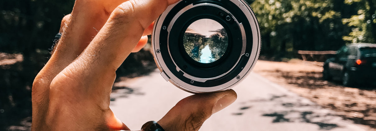 Canva - Person Holding Camera Lens in the Middle of Street Under Blue Sky